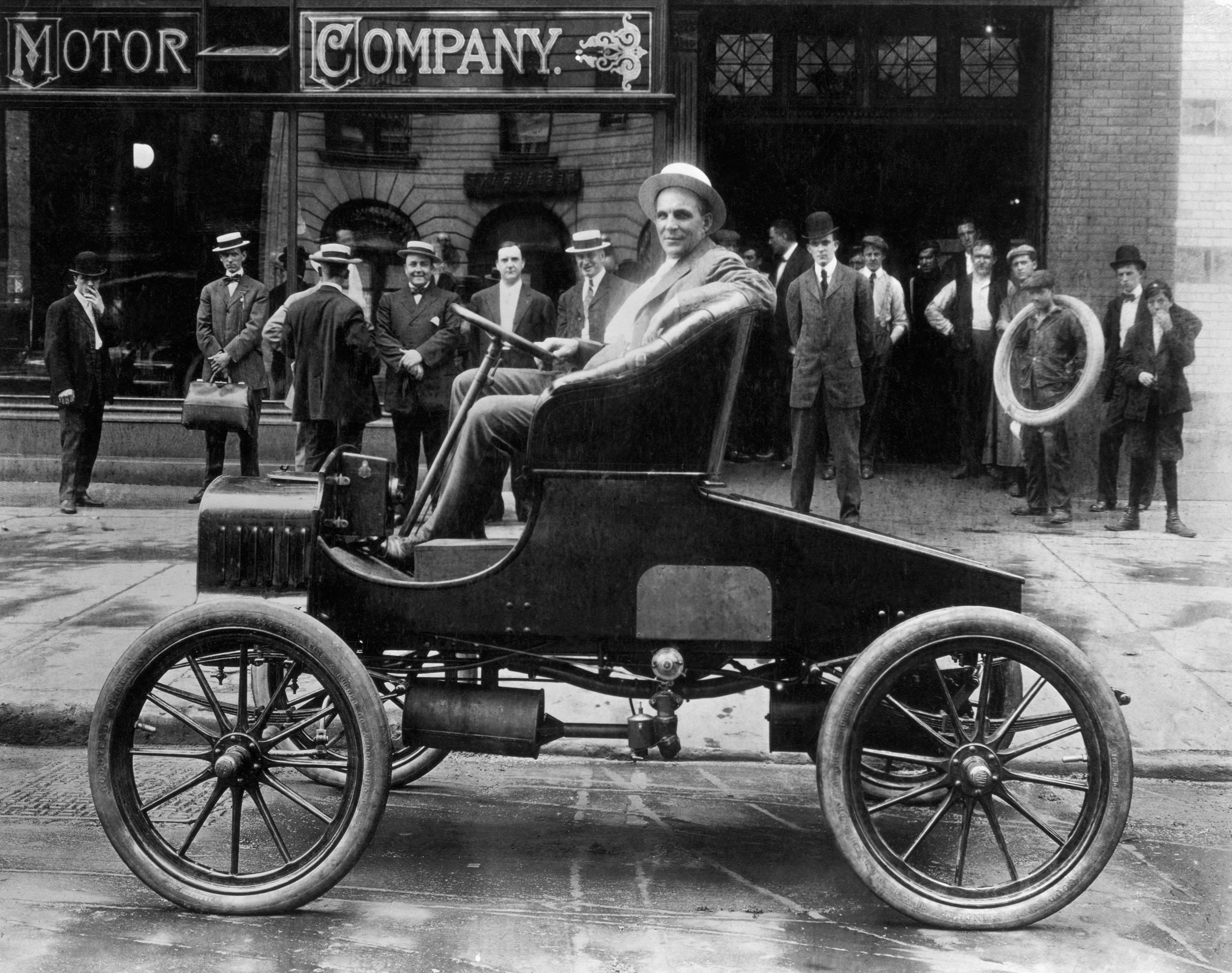 Генри Форд, сидящий в одном из своих автомобилей, сделанных в начале 1900-х годов. Датировано изображение примерно 1920 годом.